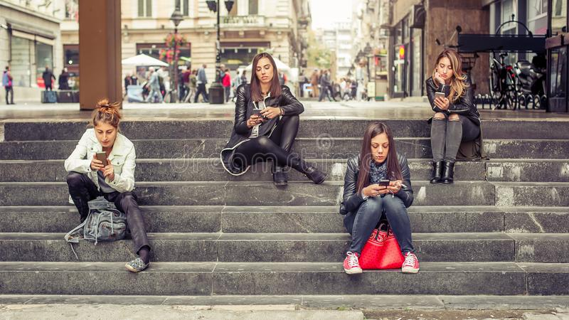 Ομάδα κοριτσιών που κάθονται στα σκαλοπάτια πόλεων με το smartphone στοκ φωτογραφία με δικαίωμα ελεύθερης χρήσης