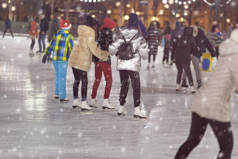 Ομάδα κοριτσιών που κάνουν πατινάζ πίσω σε μας Πάγος φίλων που κάνει πατινάζ στο πάρκο πόλεων, χιονώδες βράδυ Υγιής υπαίθρια χειμ στοκ φωτογραφία με δικαίωμα ελεύθερης χρήσης