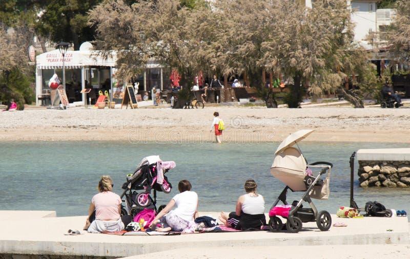 Ομάδα μητέρων με τους περιπατητές μωρών που κάθονται στην παραλία την άνοιξη εκτός εποχής στοκ φωτογραφία με δικαίωμα ελεύθερης χρήσης
