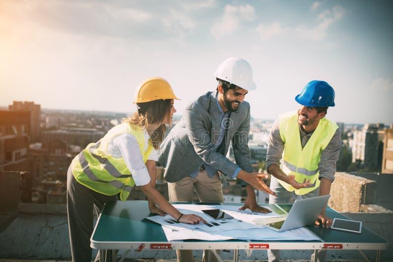 Ομάδα μηχανικών, αρχιτέκτονες, συνέταιροι στο εργοτάξιο οικοδομής που λειτουργεί από κοινού στοκ φωτογραφίες