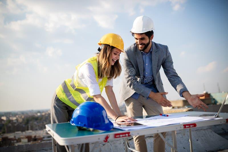 Ομάδα μηχανικών, αρχιτέκτονες, συνέταιροι στο εργοτάξιο οικοδομής που λειτουργεί από κοινού στοκ εικόνα