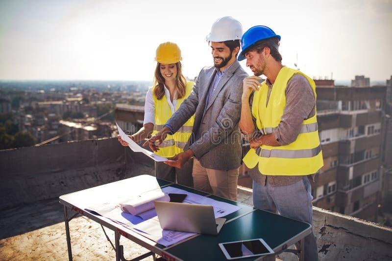 Ομάδα μηχανικών, αρχιτέκτονες, συνέταιροι στο εργοτάξιο οικοδομής που λειτουργεί από κοινού στοκ εικόνα με δικαίωμα ελεύθερης χρήσης