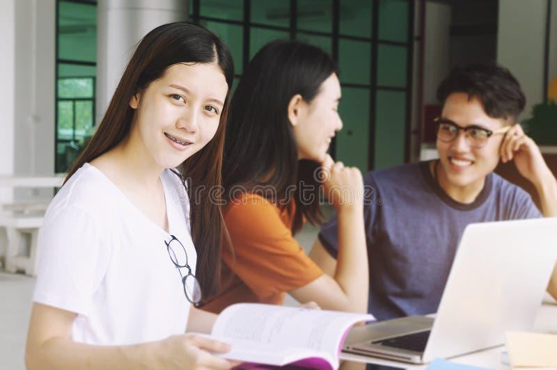 Ομάδα νέου Ασιάτη που μελετά στην πανεπιστημιακή συνεδρίαση κατά τη διάρκεια της πανεπιστημιακής πανεπιστημιούπολης νεολαίας μελέ στοκ εικόνες
