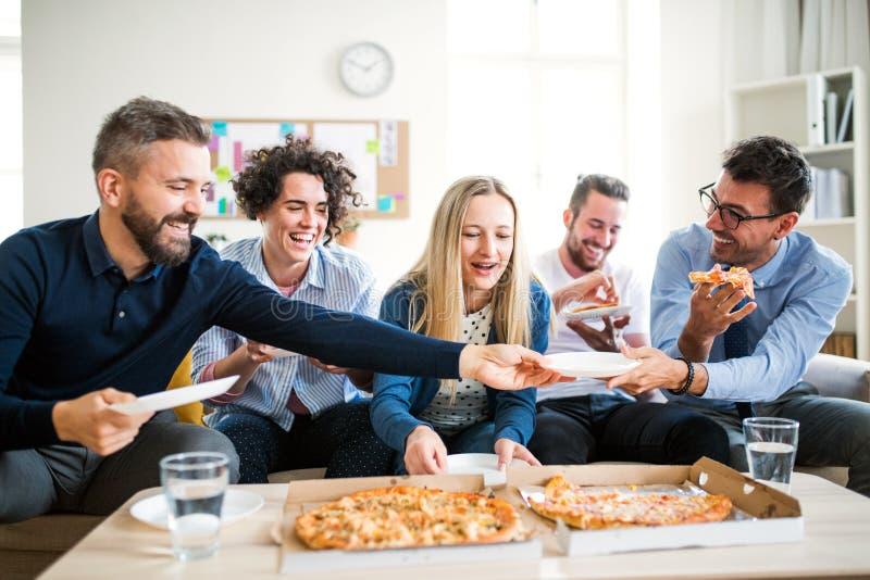 Ομάδα νέου businesspeople με την πίτσα που έχει το μεσημεριανό γεύμα σε ένα σύγχρονο γραφείο στοκ εικόνες