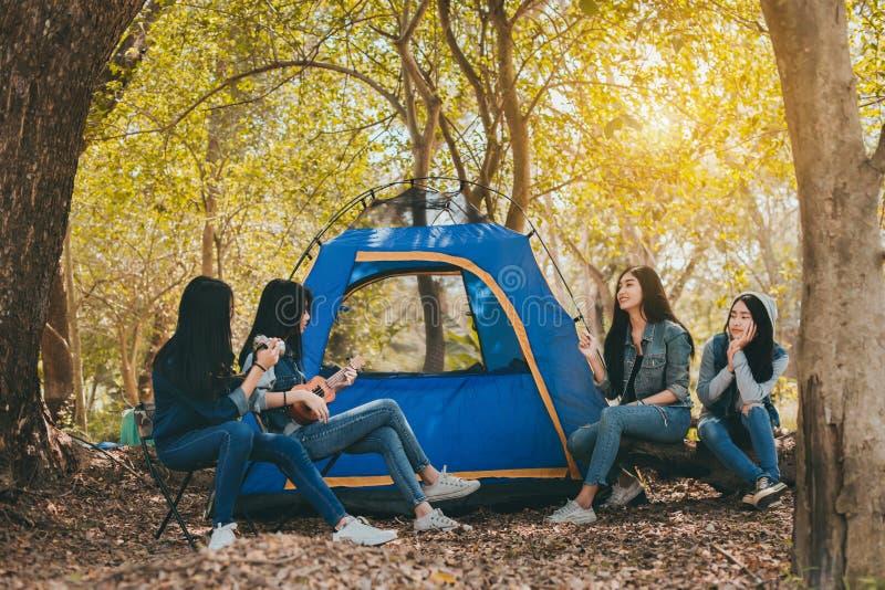 Ομάδα νέων ασιατικών γυναικών που στρατοπεδεύουν και που στηρίζονται στο δάσος στοκ φωτογραφία με δικαίωμα ελεύθερης χρήσης