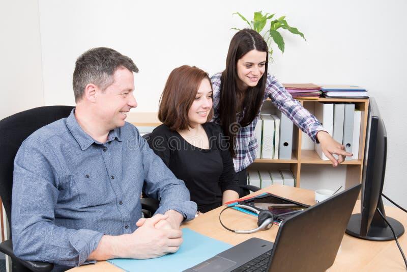 Ομάδα νέων επιχειρηματιών που εργάζονται και που επικοινωνούν καθμένος στο γραφείο που μιλά και που χαμογελά μαζί στοκ φωτογραφία με δικαίωμα ελεύθερης χρήσης