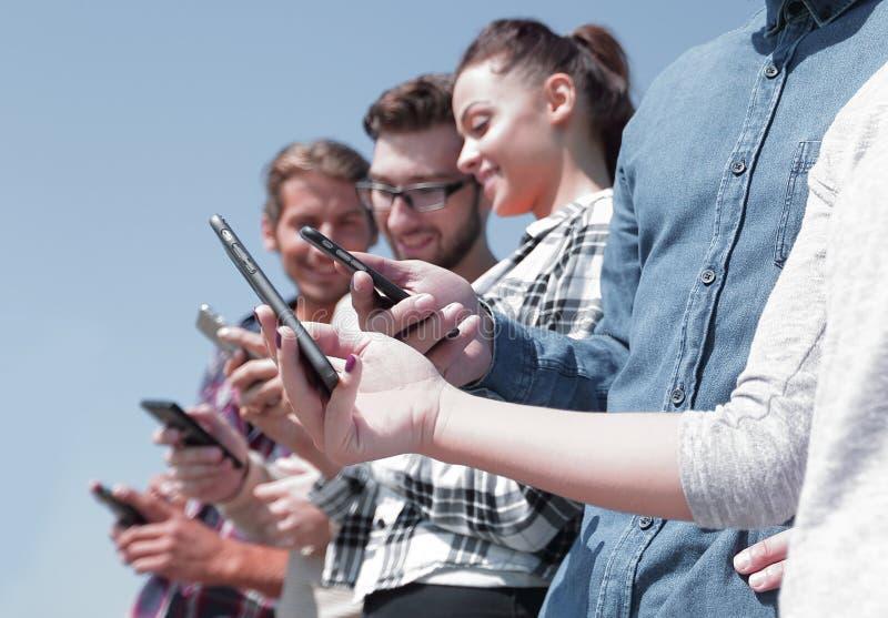 Ομάδα νέων με τις σύγχρονες συσκευές στοκ εικόνα