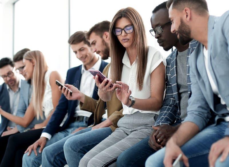 Ομάδα νέων που εξετάζουν τις οθόνες των smartphones τους στοκ εικόνες