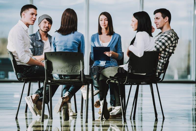 Ομάδα νέων που κάθονται στις καρέκλες στον κύκλο στοκ φωτογραφίες με δικαίωμα ελεύθερης χρήσης