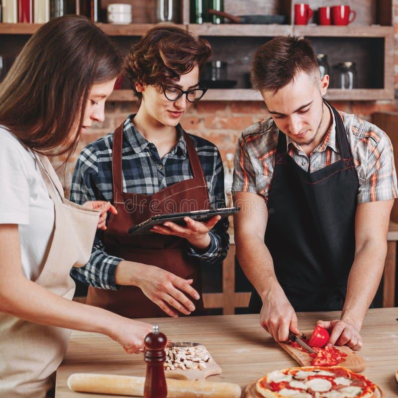 Ομάδα νέων που μαγειρεύουν από κοινού Διαβασμένη γυναίκα συνταγή στην ετικέττα στοκ εικόνες