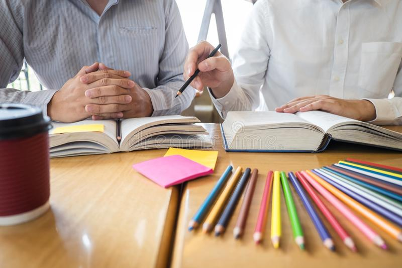 Ομάδα νέων που μαθαίνουν μελετώντας το νέο μάθημα στη γνώση στη βιβλιοθήκη κατά τη διάρκεια της βοήθειας της εκπαίδευσης φίλων δι στοκ εικόνες