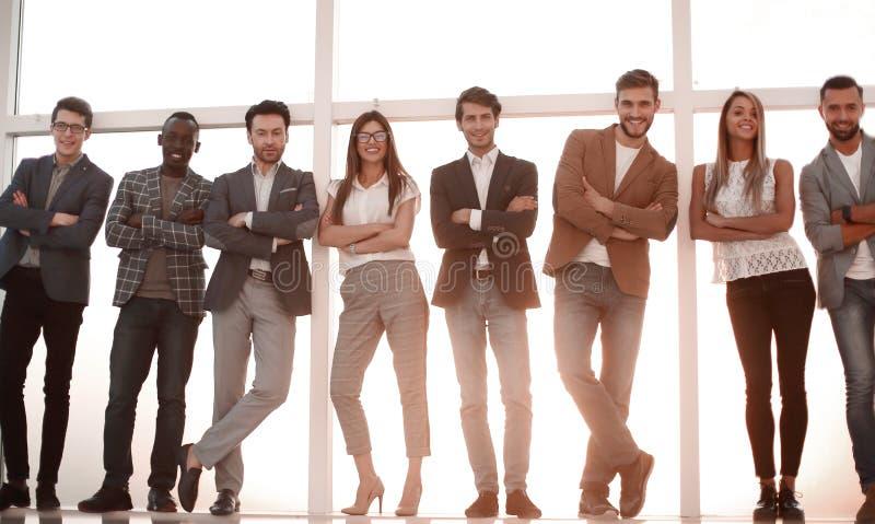 Ομάδα νέων που στέκονται σε ένα γραφείο με ένα μεγάλο παράθυρο στοκ εικόνα