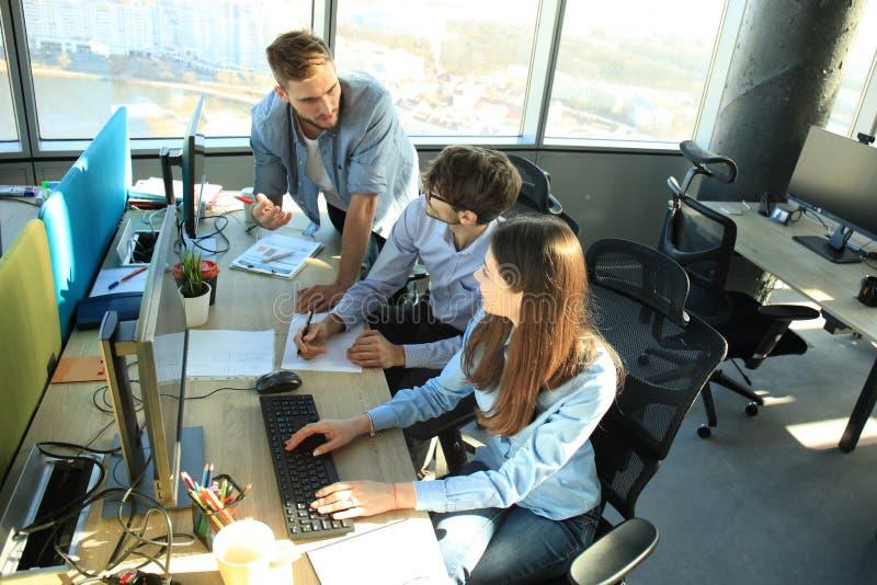 Ομάδα νέων στη συνεδρίαση περιστασιακής ένδυσης στο γραφείο γραφείων και τη συζήτηση κάτι εξετάζοντας το PC από κοινού στοκ φωτογραφίες