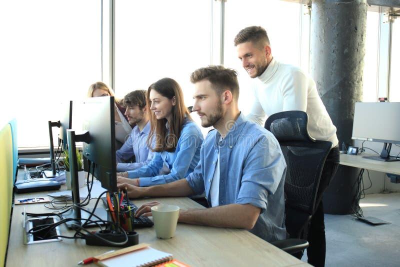Ομάδα νέων στη συνεδρίαση περιστασιακής ένδυσης στο γραφείο γραφείων και τη συζήτηση κάτι εξετάζοντας το PC από κοινού στοκ εικόνα με δικαίωμα ελεύθερης χρήσης