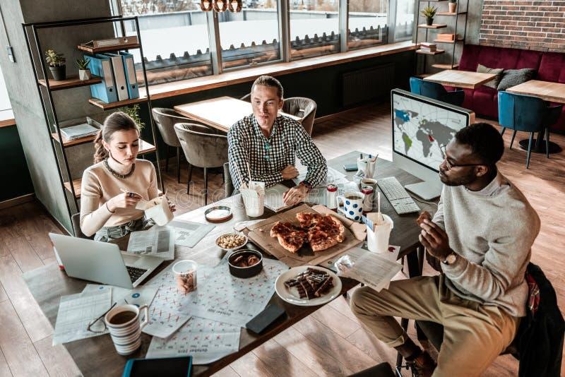 Ομάδα νέων συναδέλφων που απολαμβάνουν το γεύμα τους στοκ εικόνες