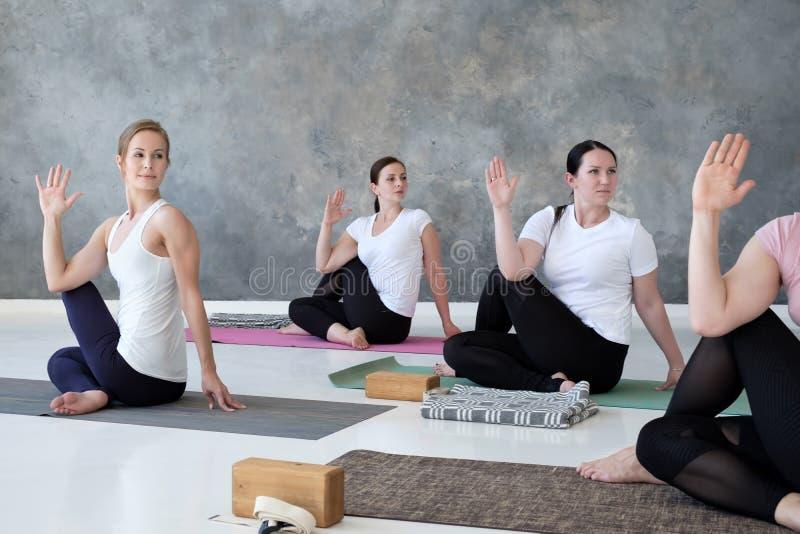 Ομάδα νέων φίλαθλων γυναικών που κάθονται στην άσκηση matsyendrasana ardha στοκ εικόνα με δικαίωμα ελεύθερης χρήσης