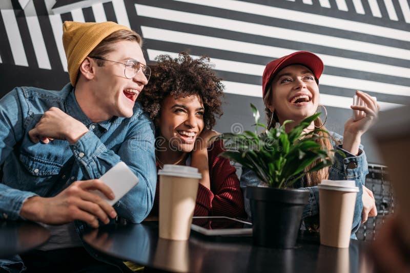 ομάδα νέων φίλων που ξοδεύουν το χρόνο στον καφέ στοκ εικόνες