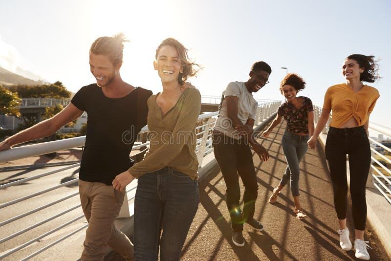 Ομάδα νέων φίλων που περπατούν υπαίθρια κατά μήκος της διόδου από κοινού στοκ εικόνες με δικαίωμα ελεύθερης χρήσης