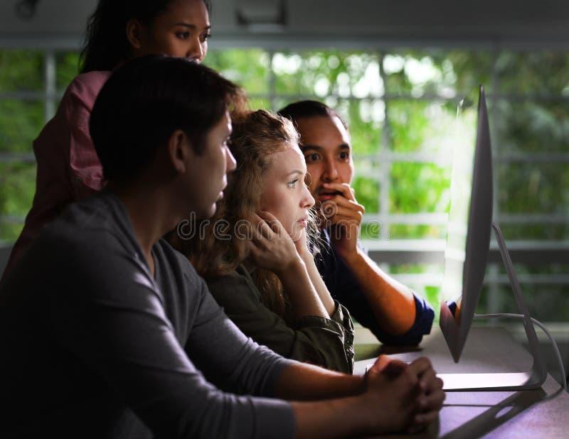Ομάδα νέων businesspersons που εξετάζει με προσήλωση την οθόνη στοκ εικόνα με δικαίωμα ελεύθερης χρήσης