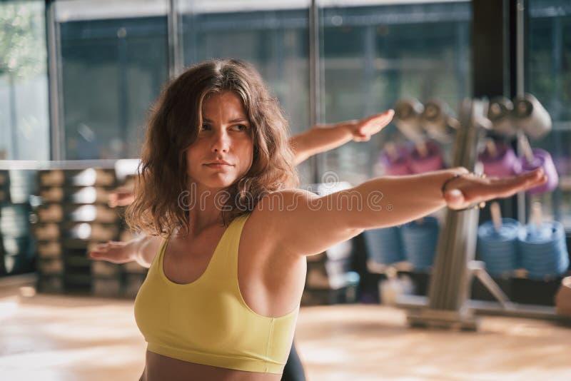 Ομάδα Νεαρές Καυκάσιες γυναίκες στα αθλητικά ενδύματα ποζάρουν πολεμιστές στο γυμναστήριο, Ιδέα της χαλάρωσης και του διαλογισμού στοκ εικόνα