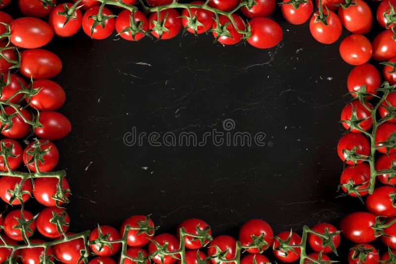 Ομάδα ντοματών κερασιών στο μαύρο μάρμαρο όπως τον πίνακα, που τακτοποιείται στο πλαίσιο γύρω, ορθογώνιο διάστημα για το κείμενο  στοκ εικόνες