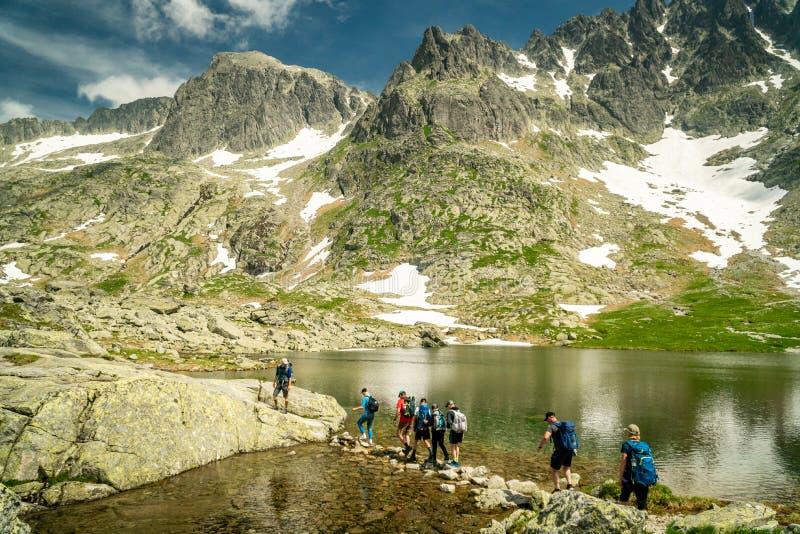Ομάδα οδοιπόρων που διασχίζουν τη λίμνη βουνών σε υψηλό Tatras, Σλοβακία στοκ εικόνα με δικαίωμα ελεύθερης χρήσης