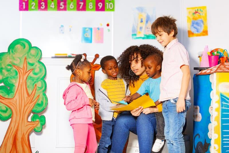 Ομάδα παιδιών που διαβάζουν το βιβλίο με το δάσκαλο στο βρεφικό σταθμό στοκ φωτογραφίες