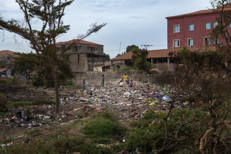 Ομάδα παιδιών που συλλέγουν τα απορρίματα σε υλικά οδόστρωσης στην πόλη του Μπισσάου, στη Γουινέα-Μπισσάου στοκ φωτογραφία με δικαίωμα ελεύθερης χρήσης