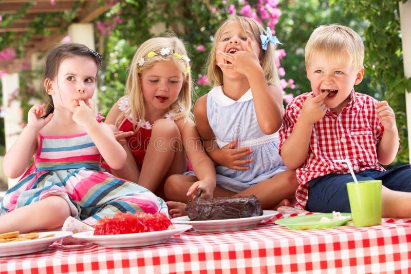 Ομάδα παιδιών που τρώνε το κέικ στο υπαίθριο συμβαλλόμενο μέρος τσαγιού στοκ φωτογραφία με δικαίωμα ελεύθερης χρήσης
