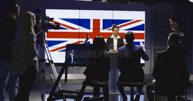 Ομάδα παραγωγής που βοηθά μια άγκυρα ειδήσεων στοκ εικόνες