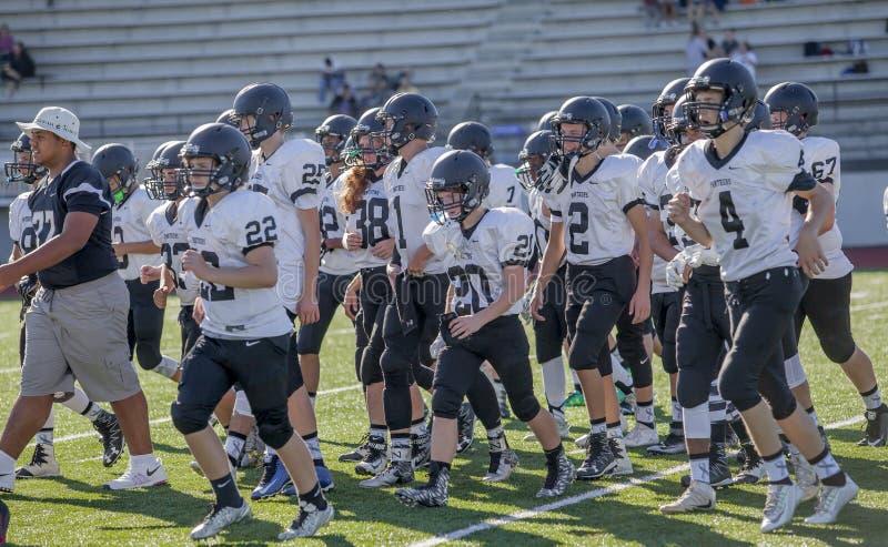 Ομάδα ποδοσφαίρου γυμνασίου στην πίσσα στοκ φωτογραφία