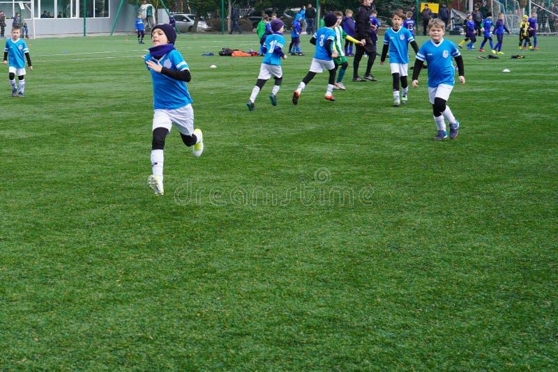 Ομάδα ποδοσφαίρου παιδιών ` s στην πίσσα Έδαφος κατάρτισης ποδοσφαίρου παιδιών Νέοι ποδοσφαιριστές που τρέχουν μετά από τη σφαίρα στοκ φωτογραφία