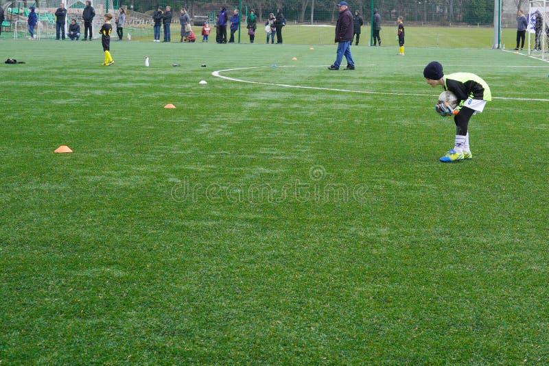 Ομάδα ποδοσφαίρου παιδιών ` s στην πίσσα Έδαφος κατάρτισης ποδοσφαίρου παιδιών Νέοι ποδοσφαιριστές που τρέχουν μετά από τη σφαίρα στοκ φωτογραφίες