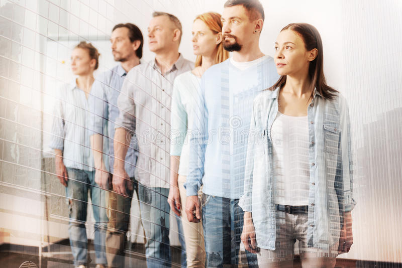 Ομάδα σοβαρών ανθρώπων που στέκονται σε μια σειρά στοκ εικόνα
