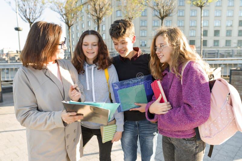 Ομάδα σπουδαστών με το δάσκαλο, έφηβοι που μιλά σε έναν θηλυκό δάσκαλο στοκ φωτογραφίες