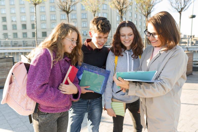 Ομάδα σπουδαστών με το δάσκαλο, έφηβοι που μιλά σε έναν θηλυκό δάσκαλο στοκ εικόνες