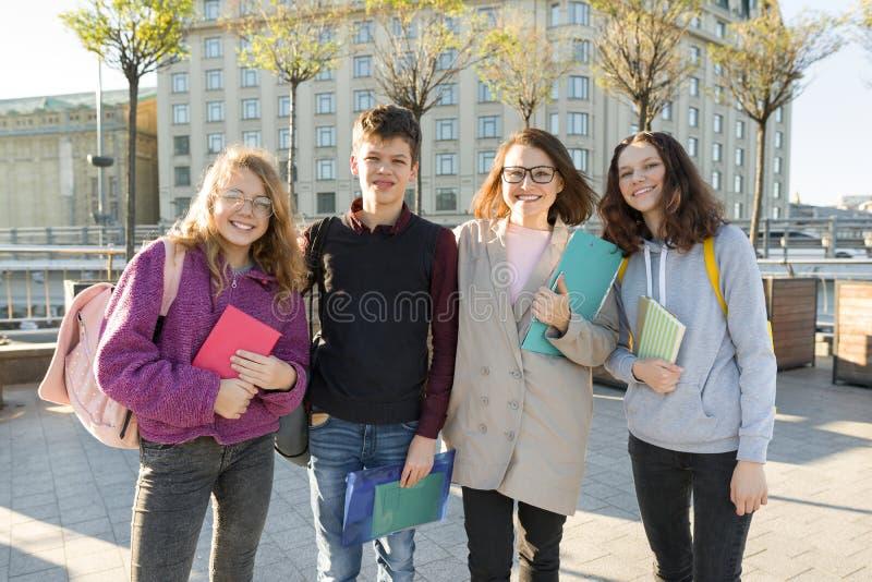 Ομάδα σπουδαστών με το δάσκαλο, έφηβοι που μιλά σε έναν θηλυκό δάσκαλο στοκ φωτογραφίες με δικαίωμα ελεύθερης χρήσης