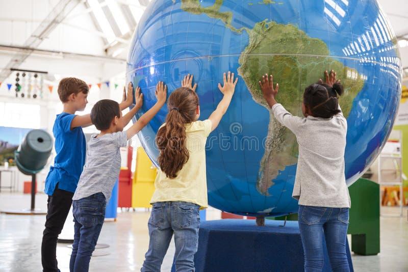 Ομάδα σχολικών παιδιών που κρατούν τη γιγαντιαία σφαίρα σε ένα κέντρο επιστήμης στοκ φωτογραφία
