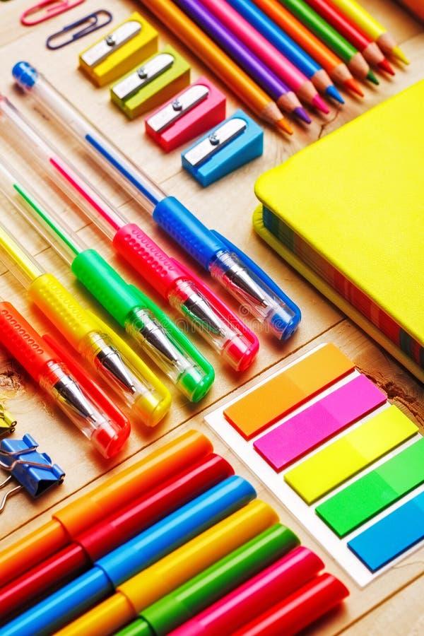 Ομάδα σχολικών προμηθειών και σημειωματάριων στον ξύλινο πίνακα στοκ εικόνα