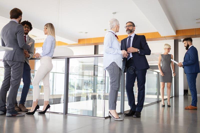 Ομάδα σύγχρονων επιχειρηματιών που κουβεντιάζουν κατά τη διάρκεια του διαλείμματος που στέκεται στο κτήριο γραφείων στοκ εικόνες
