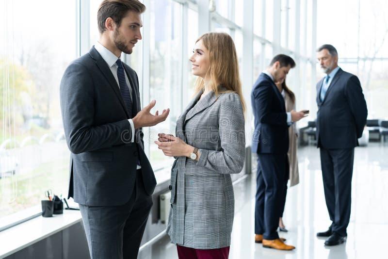 Ομάδα σύγχρονων επιχειρηματιών που κουβεντιάζουν κατά τη διάρκεια του διαλείμματος που στέκεται στην ηλιοφώτιστη αίθουσα γυαλιού  στοκ εικόνες