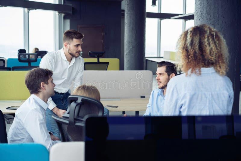 _ Ομάδα σύγχρονων νέων στην έξυπνη περιστασιακή ένδυση που διοργανώνει μια συνεδρίαση στο δημιουργικό γραφείο στοκ φωτογραφία με δικαίωμα ελεύθερης χρήσης