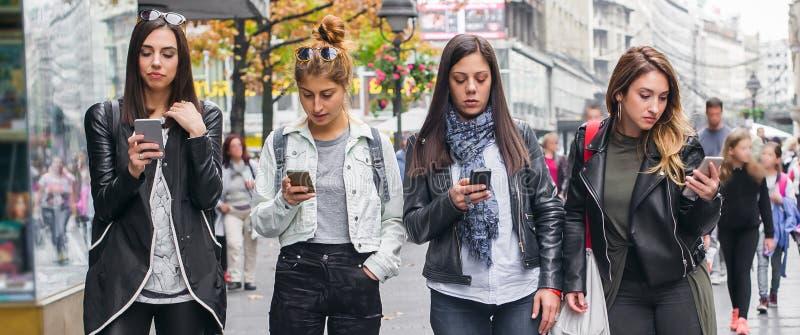 Ομάδα τεσσάρων φίλων κοριτσιών με τα smartphones στην οδό στοκ φωτογραφία με δικαίωμα ελεύθερης χρήσης