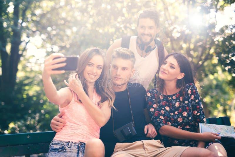 Ομάδα τεσσάρων φίλων που παίρνουν selfie με ένα έξυπνο τηλέφωνο στοκ εικόνες με δικαίωμα ελεύθερης χρήσης