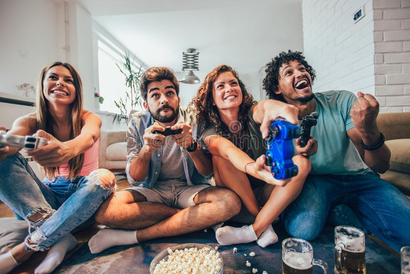 Ομάδα τηλεοπτικών παιχνιδιών παιχνιδιού φίλων μαζί στο σπίτι, έχοντας τη διασκέδαση στοκ φωτογραφία με δικαίωμα ελεύθερης χρήσης