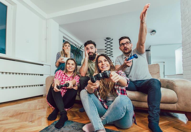Ομάδα τηλεοπτικών παιχνιδιών παιχνιδιού φίλων μαζί στο σπίτι στοκ εικόνες με δικαίωμα ελεύθερης χρήσης