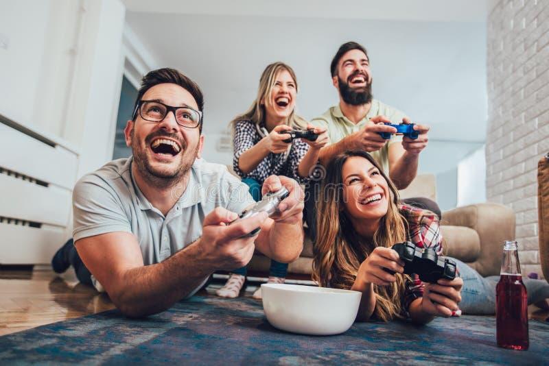 Ομάδα τηλεοπτικών παιχνιδιών παιχνιδιού φίλων μαζί στο σπίτι στοκ φωτογραφία με δικαίωμα ελεύθερης χρήσης