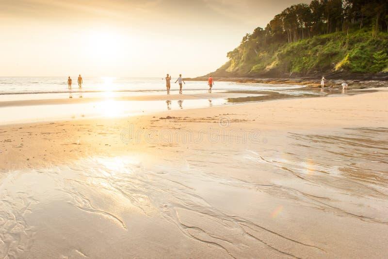 Ομάδα τουριστών που απολαμβάνουν την παραλία ηλιοβασιλέματος στοκ φωτογραφία