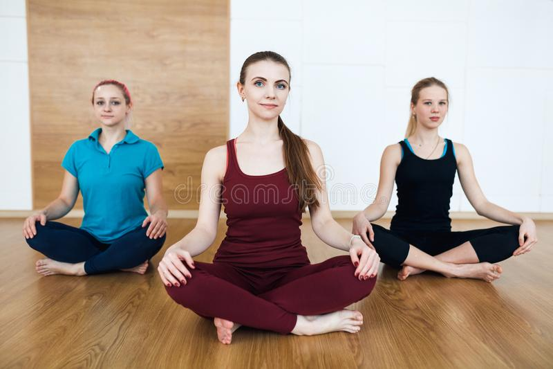Ομάδα τριών φίλαθλων νέων που ασκούν το μάθημα γιόγκας με τον εκπαιδευτικό, που κάθεται στην άσκηση Sukhasana Το κάθισμα θέτει, χ στοκ εικόνες