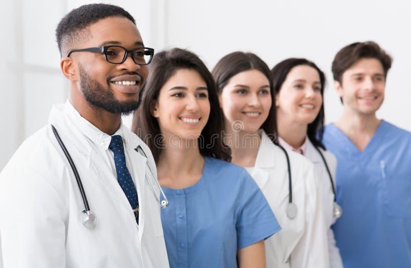 Ομάδα των γιατρών και των οικότροφων που στέκονται στο νοσοκομείο στη σειρά στοκ εικόνα